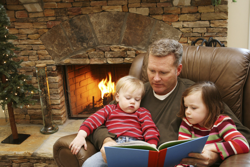Dad and kids reading in front of fire
